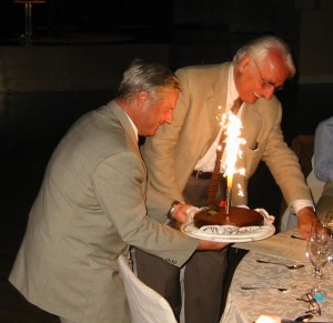 Milan Dimitrijevic and Helmut Kern holding cake with flaming candles